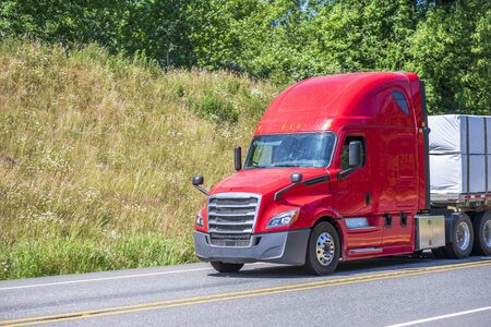 Photo pour Big rig red classic long haul semi truck with flat bed semi trailer transporting tightened packed industrial lumber boards running on the turning winding road with hills and trees in sunny day - image libre de droit