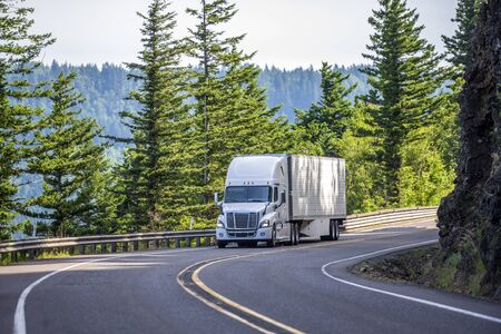 Photo for Big rig white powerful American bonnet long haul semi truck transporting commercial cargo in refrigerated semi trailer moving uphill on winding road with a green trees and safety fence on the side - Royalty Free Image