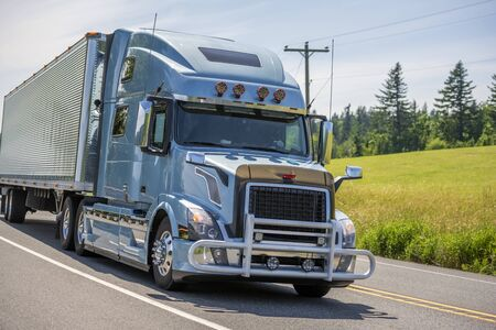 Photo for Big rig bonnet long haul blue semi truck with grille guard and chrome accessories transporting frozen commercial cargo in grooved refrigerated semi trailer driving on the summer road - Royalty Free Image