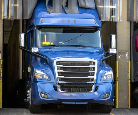 Blue big rig beautiful shape American powerful semi truck with chrome accents and refrigerated semi trailer standing in warehouse dock space for loading frozen cargo for next delivery
