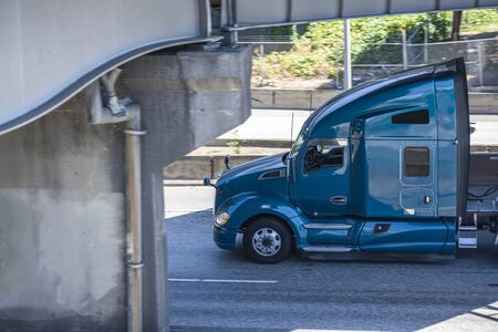 Blue big rig American bonnet semi truck with high roof transporting commercial cargo on flat bed semi trailer driving on the wide highway road under the bridge in sunny day