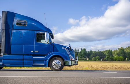 Photo pour Big rig powerful professional industrial blue bonnet semi truck for long haul delivery commercial cargo going with refrigerator semi trailer on the summer road with forest and meadows on the sides - image libre de droit