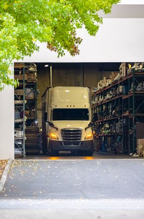 Photo for Big rig white bonnet long haul semi truck with turned on headlights and dry van semi trailer standing inside of warehouse with racks and loads for unloading delivered commercial cargo - Royalty Free Image