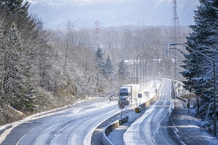 Photo pour Big rig white long haul semi truck with grille guard transporting commercial goods in dry van semi trailer driving on the turning winter snowy wet dangerous highway with trees on the sides - image libre de droit