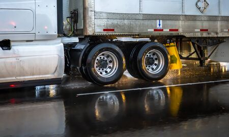Photo for Big rig classic industrial grade transportation semi truck transporting commercial cargo in dry van semi trailer driving on wet raining evening road with reflection on the highway slippery surface  - Royalty Free Image