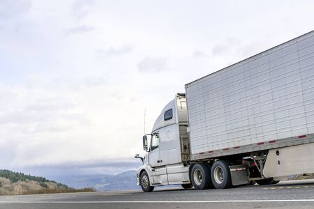 Powerful long haul big rig industrial grade diesel semi truck transporting commercial food cargo in refrigerated semi trailer running on the flat road with sky and hills view in Columbia Gorge