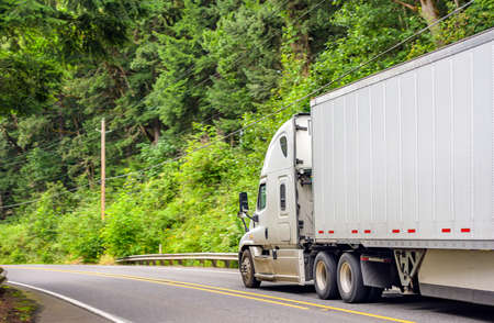Photo for White bonnet big rig long hauler industrial semi truck transporting freight commercial cargo in dry van semi trailer running on the winding road in forest at Columbia Gorge National Recreation Area - Royalty Free Image