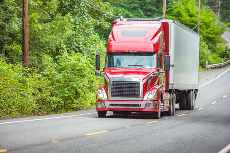 Photo for Red bonnet big rig industrial semi truck transporting freight commercial cargo in refrigerator semi trailer climbing on the winding road in forest at Columbia Gorge National Recreation Area - Royalty Free Image