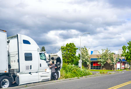 Photo for Broken day cab industrial big rig white semi truck tractor for heavy-duty freights standing with open hood on the road waiting for a mobile repair team and a towing truck to tow to a repair shop - Royalty Free Image