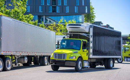 Photo pour Medium duty professional freight powerful rigs industrial diesel semi trucks with refrigerated box trailers running to warehouse dock for loading cargo for the next delivery - image libre de droit