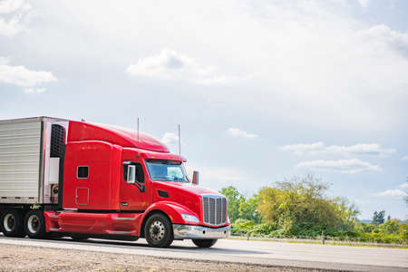 Photo for Bright red long hauler big rig red industrial semi truck transporting frozen and chilled foods in refrigerator semi trailer running on the straight highway road with green trees on the side - Royalty Free Image