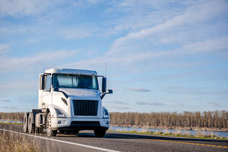 Photo for Powerful Big rig white day cab semi truck tractor without semi trailer running on the narrow highway road along the river to warehouse for pick up the next loaded trailer for delivery - Royalty Free Image