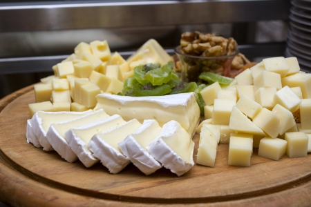 Assorted cheese and dried fruits on a wooden board