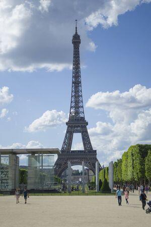 Photo pour Paris, France - 6th June, 2019: Eiffel Tower view from far. Tourists walk around the sights. Vertical. - image libre de droit