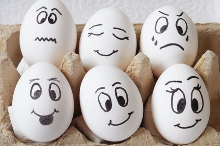 white eggs with different faces in a packet