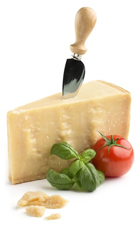 chunk of parmesan cheese with basil and tomato on white background