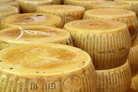 close up of a heap of  wheels of seasoned parmesan