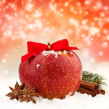 Photo pour apple with red ribbon and spices in the snow - image libre de droit