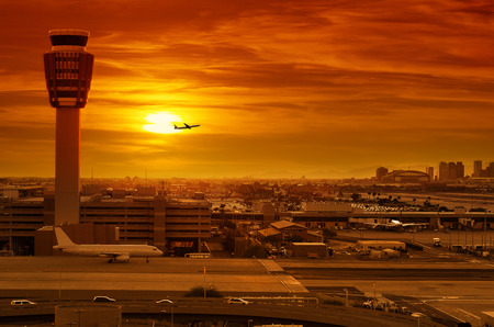 Photo pour airport control tower and airplane taking off at sunset - image libre de droit