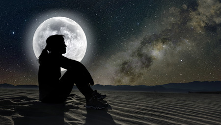 Photo pour profile of a woman sitting on sand in the moonlight - image libre de droit