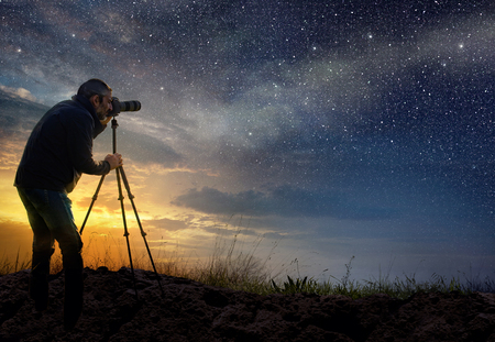 Photo pour man taking a photo at dawn with starry sky - image libre de droit
