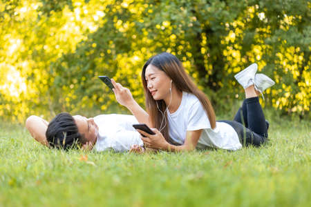 Photo for young asian couple lying down in the park listening music and relaxing with smartphones, boy and girl in love looking in each others eyes - Royalty Free Image