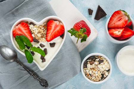 Yogurt with muesli and strawberries in a heart-shaped bowl on a pastel blue background.