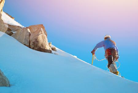 Photo pour Mountaineer reaches the top of a snowy mountain - image libre de droit