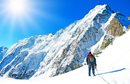 Photo pour Mountaineer sport. A climber reaching the summit of the mountain - image libre de droit