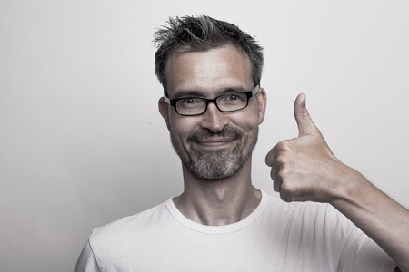Agreeing man with stubbly beard holds his thumb up