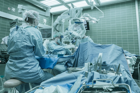 Photo pour Brain surgery using surgical microscope in a neurosurgical operating room - image libre de droit