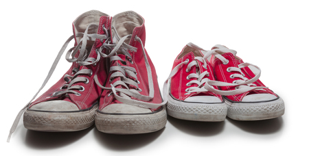 two pairs of old and new red basketball sneakers isolated on white background