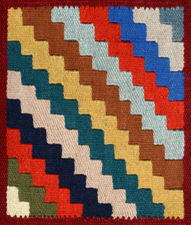 Closeup of decorative carpet fabric pattern with multi-colour bright geometrical ornament in the form of zigzag diagonal strips