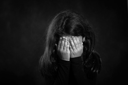 Black and white photo  Portrait of a crying girl  She is covering her face