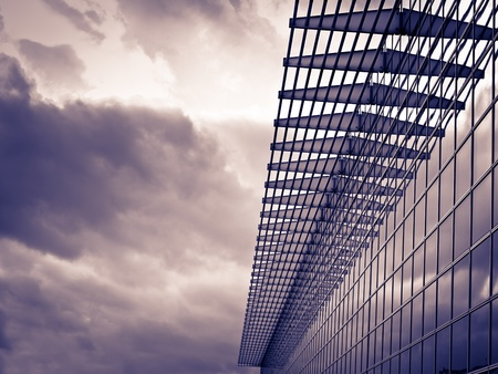 Photo pour Modern glass building on the cloudy weather, toned image, for architecture,business,construction,real estate themes - image libre de droit