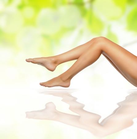 healthy sexy slender female legs over green natural spring background - spa and healthcare concept の写真素材