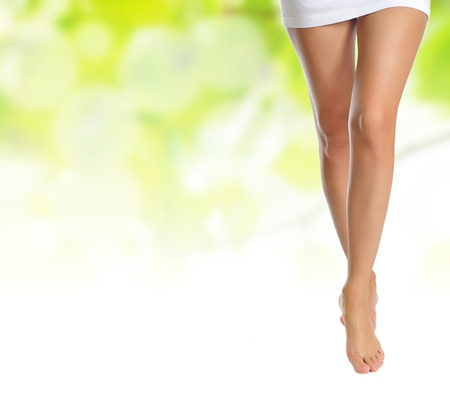 sexy naked slender female legs making step over green natural backgroundの写真素材