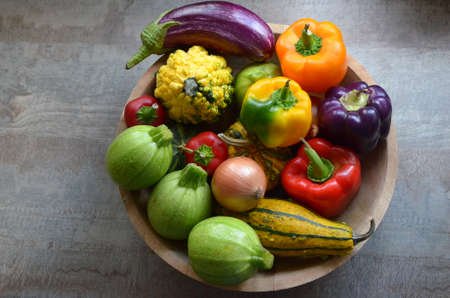 Photo for A wooden bowl with fresh organic autumn vegetables: zucchinis, pumpkins, red, orange and purple paprika, onions, eggplant - Royalty Free Image