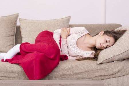 Photo for Young woman lying on a bed covered with blanket, holding her stomach in pain - Royalty Free Image