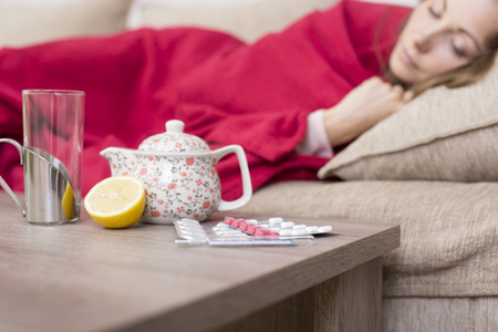 Sick woman covered with a blanket lying in bed with high fever and a flu. Pills, teapot and lemon on the table. Selective focus on the pills