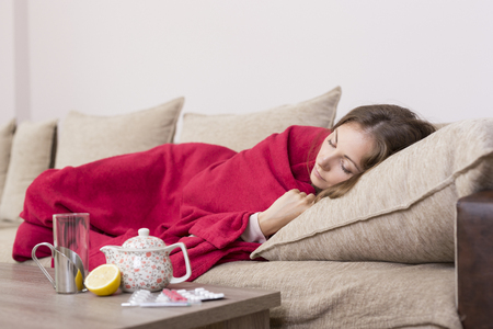 Sick woman covered with a blanket lying in bed with high fever and a flu. Pills, teapot and lemon on the table