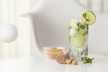 Mojito cocktail with lots of ice, white rum, lemon juice and tonic, decorated with lime slices and mint leaves on a modern white table with ice crusher and bowl of brown sugar next to it