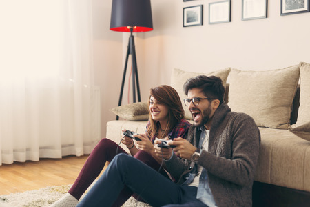 Photo pour Couple in love enjoying their free time, sitting on the living room floor, playing video games and having fun. Focus on the woman - image libre de droit