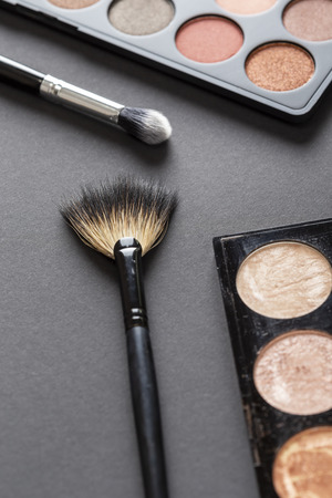 Photo for High angle view of an eyeshadow palette, highlighter palette, highlighter make up brush and an eyelid make up brush - Royalty Free Image