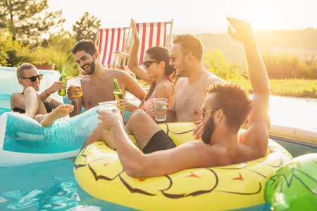Photo for Group of friends at a poolside summer party, having fun in the swimming pool, drinking cocktails and beer and making a toast - Royalty Free Image