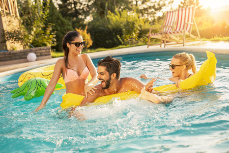 Photo pour Group of friends at a poolside summer party,  having fun in the swimming pool, splashing water and fighting over a floating mattress - image libre de droit