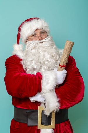 Photo for Portrait of a Santa Claus holding a letter with a list of children and their wish list for New Year presents - Royalty Free Image