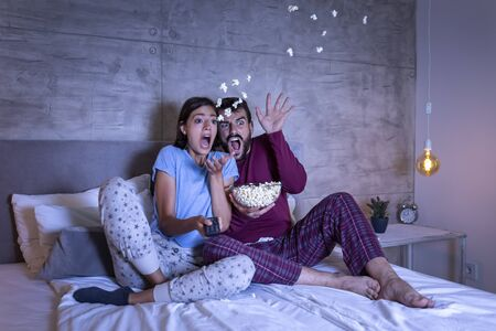 Photo for Beautiful young couple in love, sitting in bed side by side, eating popcorn and having fun watching a horror movie at night - Royalty Free Image