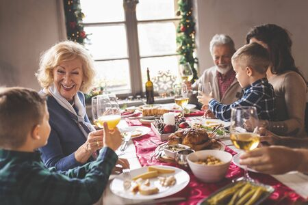 Photo pour Happy family celebrating Christmas, having dinner at home, making a toast with glasses of wine and orange juice and enjoying their time together - image libre de droit