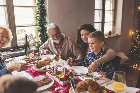 Photo for Family having Christmas dinner at home, gathered around the table, enjoying their time together; mother holding son in her lap and smiling - Royalty Free Image